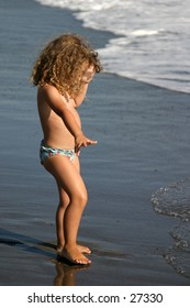 little girl playing along the water
