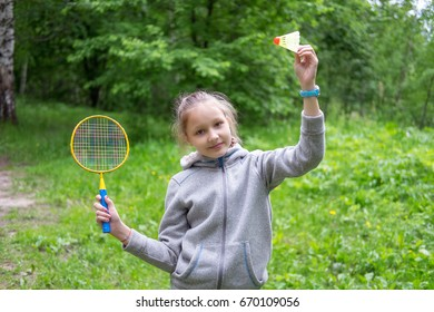 Little girl playing badminton on the street