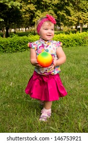 little girl playing with a ball on the nature