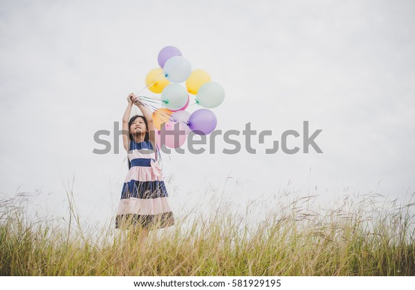Little girl playing with balloons on meadows field.