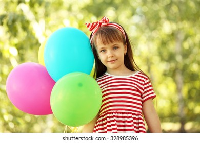Little girl playing with balloons in the park