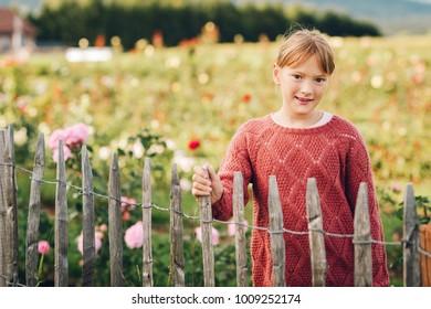 Little girl playing in beautiful rose garden