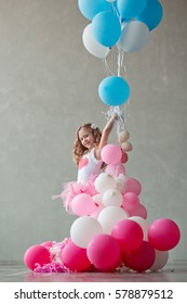 Little girl playing in a beautiful skirt with balloons pink color. Childhood. The occasion.