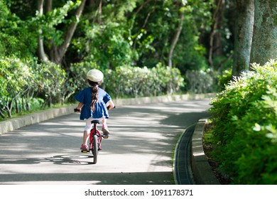 Little girl playing with bicycle