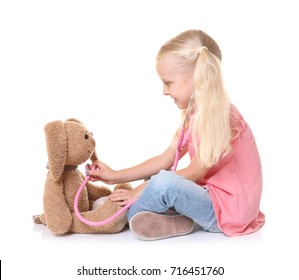 Little girl playing with bunny and stethoscope isolated on white