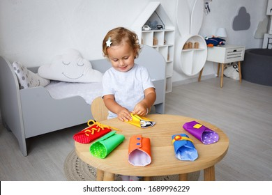 Little girl playing with buttons and zipper on the table for developing fine motor skills