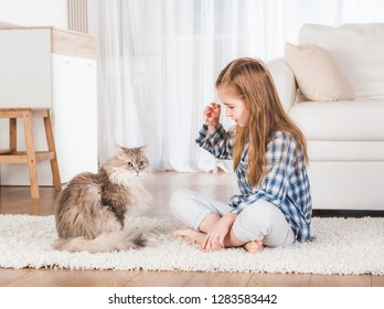 Little girl playing with cat at home