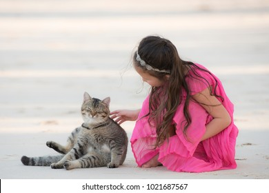 Little girl playing with a cat on the beach