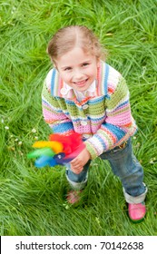 Little girl playing with colored pinwheel