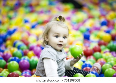 little girl is playing in colorful balls