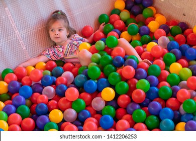Little girl playing with colorful plastic balls on the playground. Top view