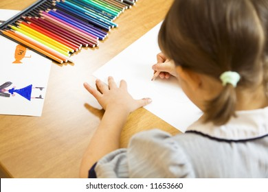 little girl playing with colors. The focus is on the hand drawing