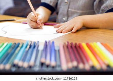 little girl playing with colors. The focus is on the hand laying on the paper