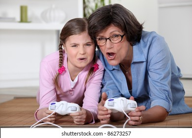 Little girl playing a computer game with her grandma