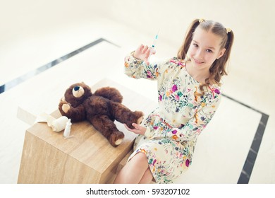 Little girl playing doctor at home, ready to make vaccination shot with medicine syringe to her toy teddy bear