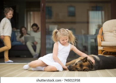 Little girl playing with dog outside, stroking german shepherd lying on porch, parents with small boy spending time inside home at background, leisure of cozy warm happy family in country house