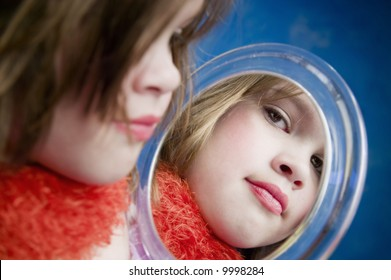 Little Girl Playing Dress-Up Looking in a Handheld Mirror