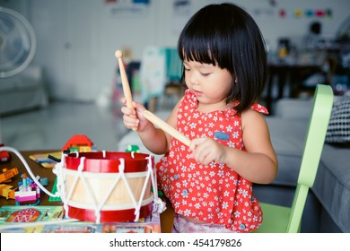 Little girl playing drum at home.Child development concept.