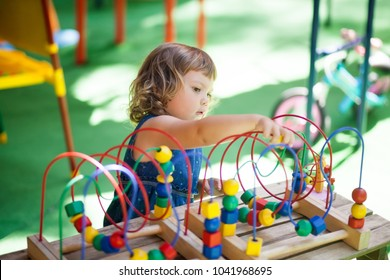 little girl playing with educational toy - labyrinth. kindergarten concept, lifestyle. Early education and development.
