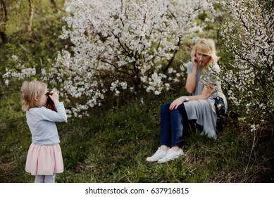 Little girl is playing in a flowery garden with her mother and taking pictures of her