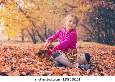 Little girl playing in the forest with golden leaves