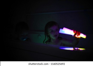 Little girl playing with glow sticks in the bathtub with her little brother