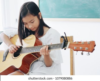 The little girl playing guitar in the class room.