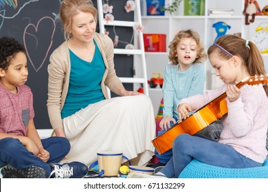Little girl playing the guitar during music classes in kindergarten