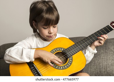 Little girl playing guitar sitting on the sofa at home