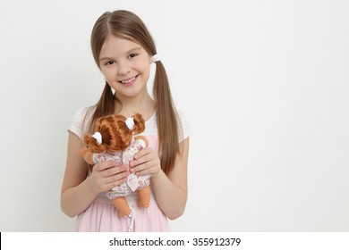 Little girl playing with her baby doll and pretending mom/little girl and doll