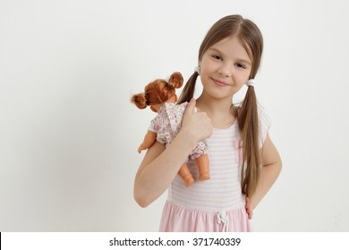 Little girl playing with her baby doll and pretending mom/Caucasian little girl and doll