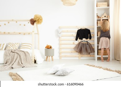 Little girl playing in her beige and white modern bedroom