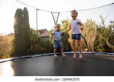 Little girl playing with her brother in backyard