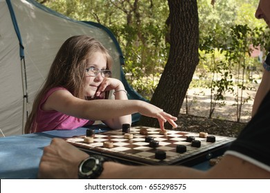 Little girl playing with her father draughts board outdoor (camping) in the sunny summer day. The touristic tent in background. Education, summer, active recreation and touristic concept
