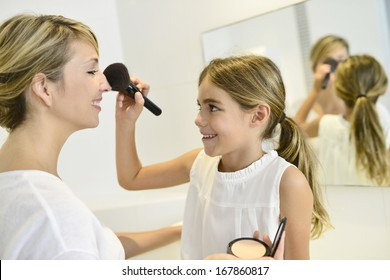 Little girl playing with her mom's makeup