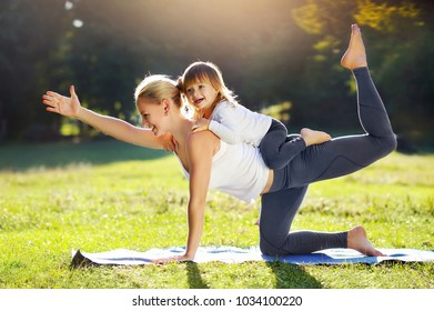 Little girl is playing with her sportive mother practicing yoga cat pose together