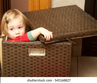 Little girl playing hide and seek in brown box