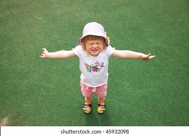 Little girl playing hide-and-seek with closed eyes