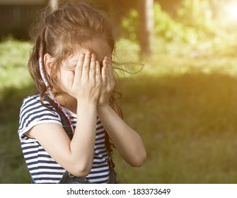 little girl is playing hide-and-seek hiding face , shy child portrait