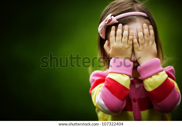 kleines Mädchen spielt VersteckGesicht