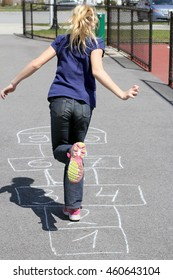 Little girl playing hopscotch on playground outdoors, children outdoor activities