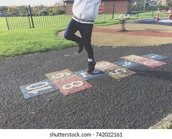 Little girl playing hopscotch at the park.