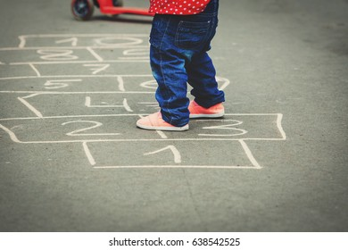 little girl playing hopscotch at playground