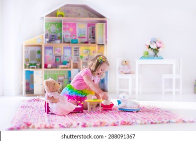 Little girl playing. Kids with doll house and stuffed animal toys. Children sit on a pink rug in a play room at home or kindergarten. Toddler kid with plush toy and dolls. Birthday party for child.