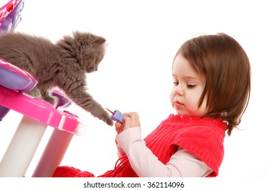 Little girl playing with with kitten and nail polish near toy bureau