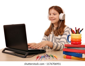 little girl playing laptop and listening music on headphones