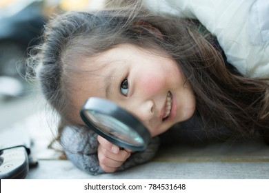 Little girl playing with magnifying glass