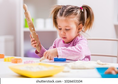 Little girl is playing and making cookies in kitchen.