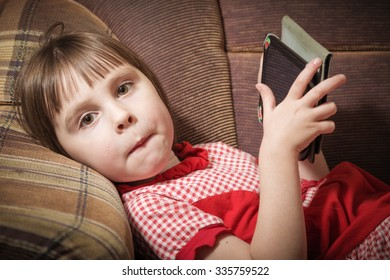 Little girl playing with a modern digital tablet in a room.