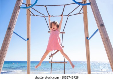 Little girl playing Monkey bars on the beach